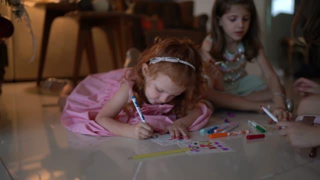vídeos de stock e filmes b-roll de small cute girls writing letter to santa at home - christmas card