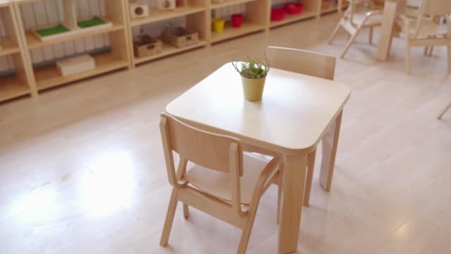 Small desk and chairs in bright preschool classroom