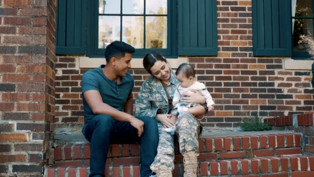 Small family is reunited after female soldier's return from military assignment A small family sit on the steps outside their home after the mid adult mom returns from military assignment. The woman sits on the steps and talks with her husband while holding their baby girl. veteran stock videos & royalty-free footage
