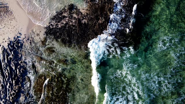 Small foamy waves rolling, drone view on blue turquoise ocean, breaking waves and whitewash. Sunny day over the sea. Colourful swells and foaming video