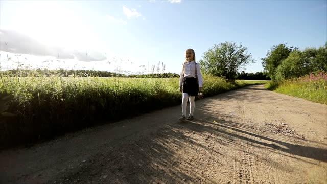 Pequeña muchacha de camisa blanca y falda negra va a la escuela por el camino arenoso - vídeo