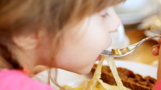 small girl is eating pasta - pinolo video stock e b–roll