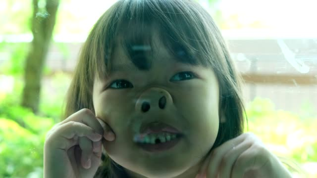 liten flicka som gör en rolig uttrycksfull grimace ansikte och sticker ut tungan. - människohuvud bildbanksvideor och videomaterial från bakom kulisserna