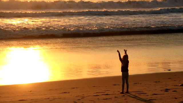 Small girl meditating on beach at sunset video