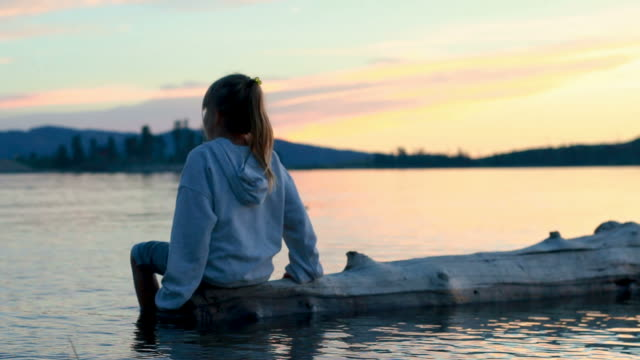 Small girl on floating tree on scenic lake at sunset video