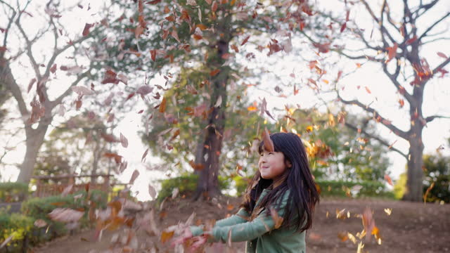 Small girl playing with fallen leaves in public park
