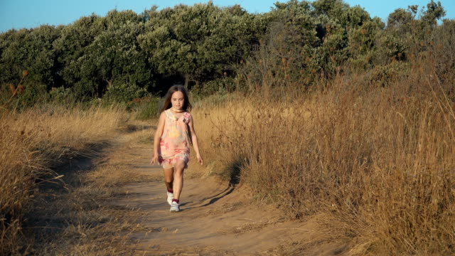 Small girl running and jumping on country road video