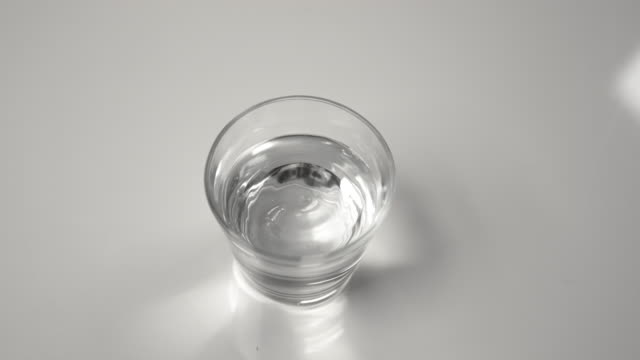 CLOSE UP: A small glass filled with water shakes during an earthquake.
