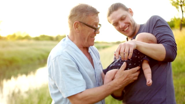 a small grandson, grandfather and father. three generations of men. family day. a man hands over his newborn son to his grandfather - grandparents stock videos & royalty-free footage