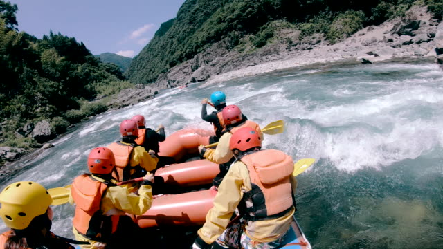 Small group of men and women white water river rafting Small group of men and women white water river rafting in a forested valley in Japan. recreational pursuit stock videos & royalty-free footage
