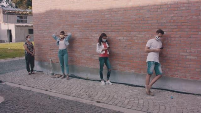vidéos et rushes de petit groupe de personnes attendant dans la ligne sur la rue de ville - faire la queue
