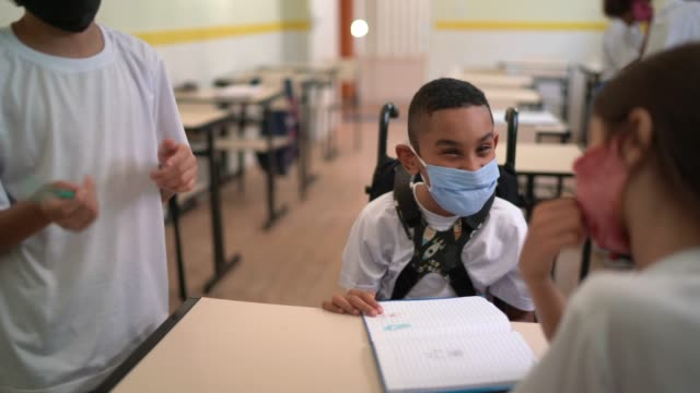 Small group of students wearing face mask studying together at school video