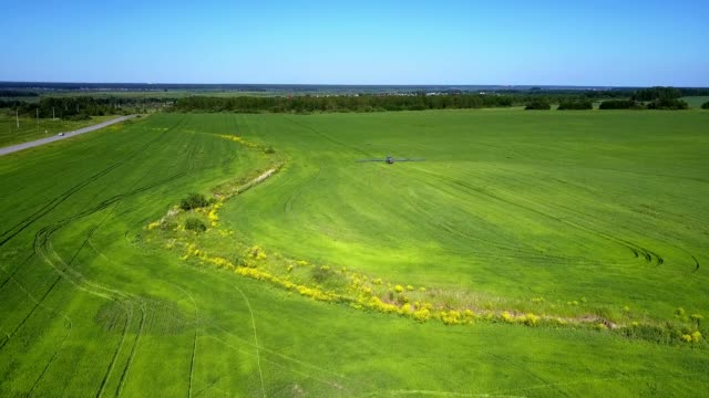 small gully among green fields with machinery