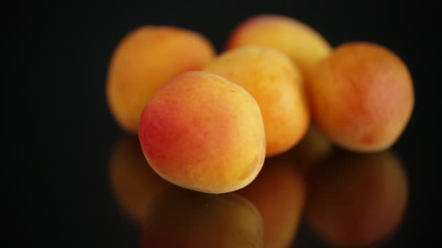 small handful of ripe apricots on black background video