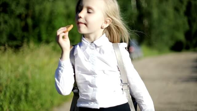 Una hambre pequeña rubia colegiala va a la escuela en el camino de arena por el campo y come una galleta. - vídeo