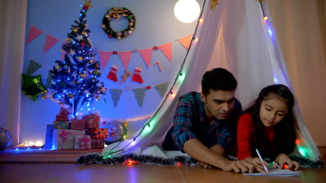Small Indian girl enjoying drawing with her dad while lying together in the tent - Christmas fun A young handsome father helping his daughter in completing her Christmas painting with colorful Christmas decorations indian family stock videos & royalty-free footage