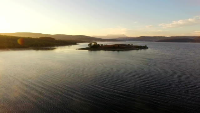 aerial view. small island in the middle of water reservoir at sunset - paesaggio marino video stock e b–roll