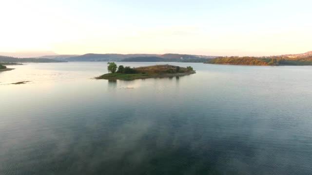 aerial view. small island in the middle of water reservoir - krajobraz morski filmów i materiałów b-roll