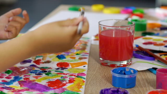 Small kid blends all possible colors on a piece of paper, imaginative mind video