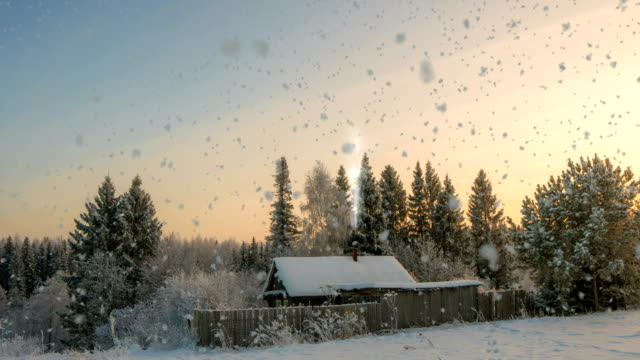 a small log cabin near the forest, a beautiful snowfall in the sunset, a beautiful winter landscape. video loop, cinemagrapf - уютный стоковые видео и кадры b-roll