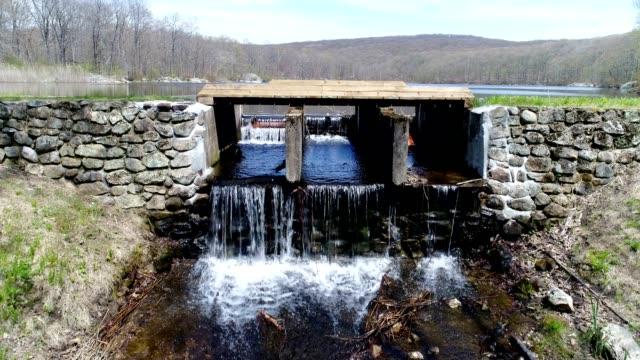 Small man made dam flowing water along lake