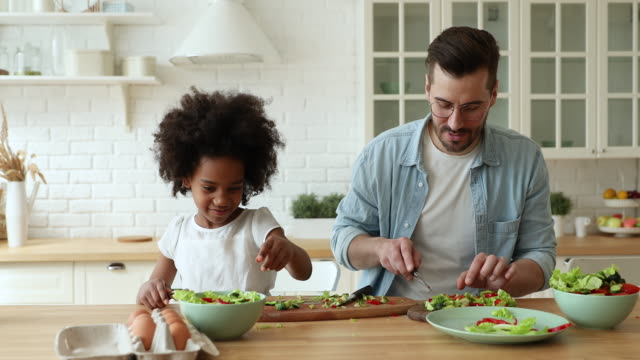 Small mixed race adopted daughter preparing food with caucasian father.