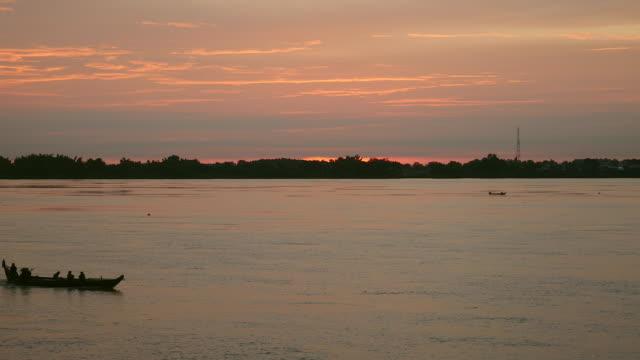 vidéos et rushes de petit bateau à moteur de procéder au lever du soleil sur la rivière - lac reflection lake