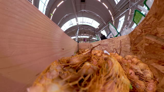 Small onions inside the net on a wooden box Small onions inside the net on a wooden box inside the storage store in the city onion stock videos & royalty-free footage