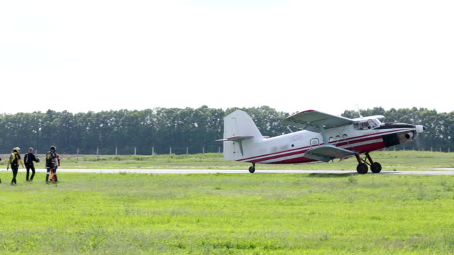 A small plane has landed on the runway and is waiting for a new group of paratroopers.