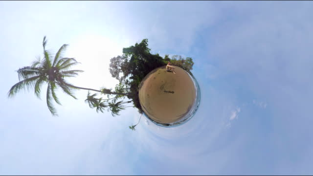 Small Planet Effect of a man sitting on the beach video
