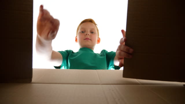 顔にポジティブな感情と感情を持つ小包ボックスを見て小さな赤い髪の少年。若い子供がカートンボックスを開き、それから贈り物を引き出す。喜びと驚きを示す小さな子供。スローモーシ� - プレゼント点の映像素材/bロール
