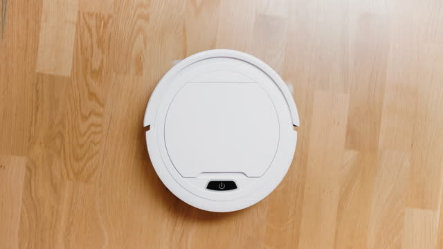 a small robot vacuum cleaner at home - automatico video stock e b–roll