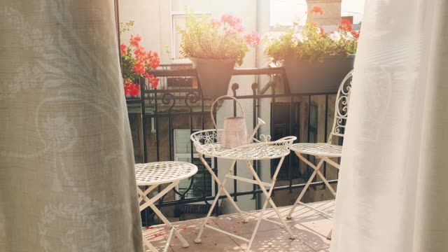 small romantic balcony with flower boxes and curtains blowing in the wind - balcone video stock e b–roll