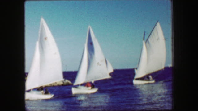 1959: Small sailboats coming into port riding wind full sails personal watercraft.