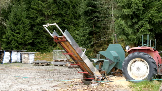 Small sawmill in the village. A tractor and a saw stand in the woods, alongside cut and packaged logs video