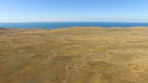 aerial: small sea island with plateau on steppe hills - horyzont wodny filmów i materiałów b-roll