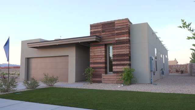 Small Southwest Modern Home Exterior Rising with Tree angled shot of a small exterior southwest home rising with a tree in the foreground facade stock videos & royalty-free footage