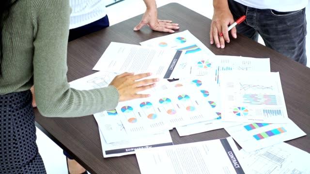 小規模なチームの会議。テーブル上のドキュメントとブレーンストーミング アジア ビジネス人々 のグループ。マルチ倫理ビジネス チーム スタート ups コンセプト。 - オンライン会議点の映像素材/bロール