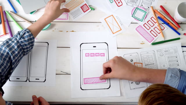 vídeos de stock e filmes b-roll de small team of ux designers creating mobile app layout - design