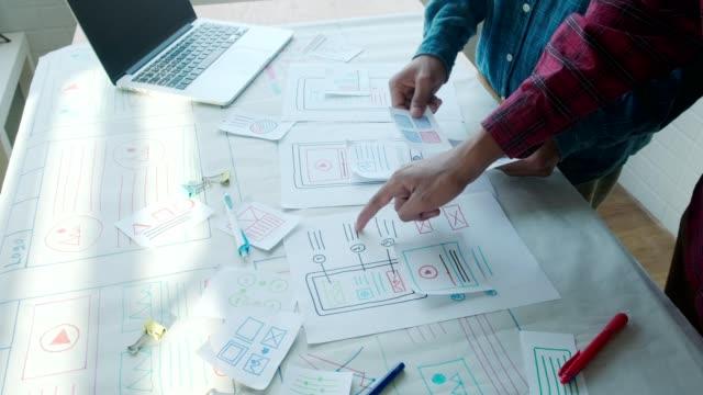 vídeos de stock e filmes b-roll de small team of young ux ui designers creating mobile app layout website - software de computador