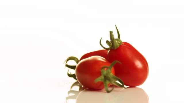 small tomatoes rotating on white background - video