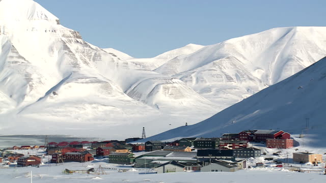 Small town Longyearbyen among snow-capped mountains of the Norwegian archipelago of Svalbard in early spring. video
