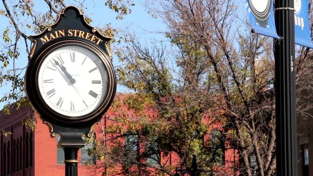 vídeos de stock, filmes e b-roll de cidade pequena main street-relógio - centro da cidade