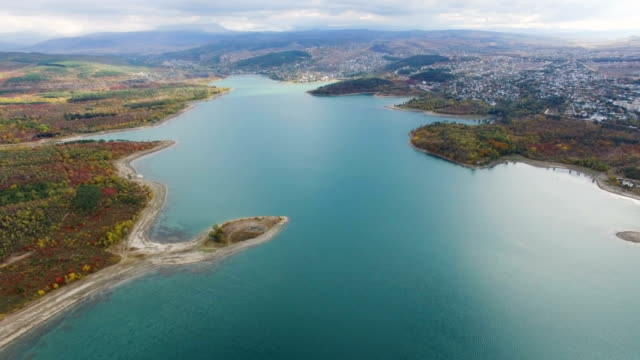 vídeos de stock e filmes b-roll de aerial: small town near beautiful turquoise lake - multicóptero