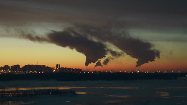 Small town stands near an icy river, white smoke comes from white and red pipes.