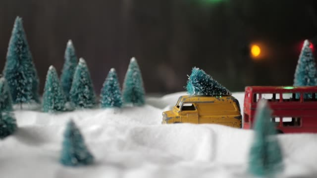 A small toy yellow toy car with a Christmas tree on the roof slowly rides through a miniature toy forest with snowdrifts and Christmas trees.
