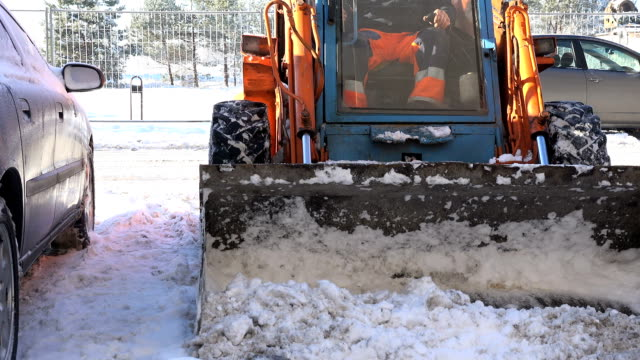small tractor clean winter snow in block flat house parking in winter. VILNIUS, LITHUANIA - JANUARY 11, 2016: small tractor excavator work clean snow near flat block houses cars on street parking in winter on January 11, 2016 in Vilnius, Lithuania. Static shot. plowing stock videos & royalty-free footage