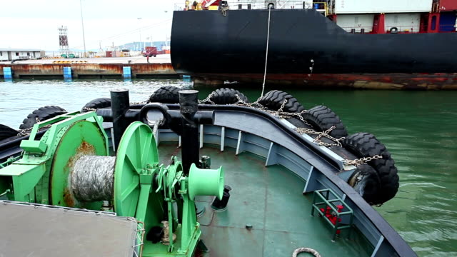 Small tug boat assisting bulk cargo ship. video