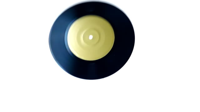 Small vinyl record flies and rotates on a white background in slow motion video
