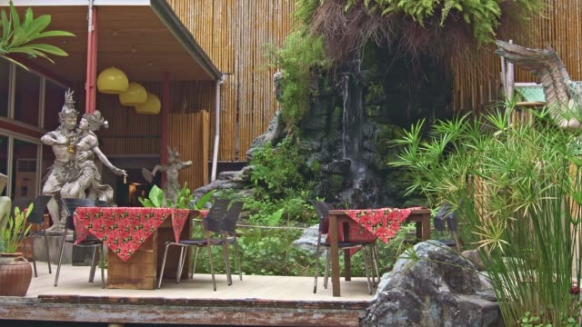 Small waterfal in the house garden with two tables and chairs. Garden in Asia style with two beautiful statues.
